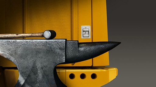 A hammer and anvil sit against a piece of construction equipment