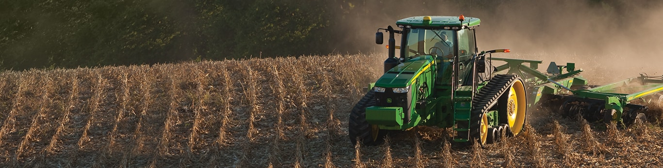 A tracked John Deere tractor moves through an already harvested field