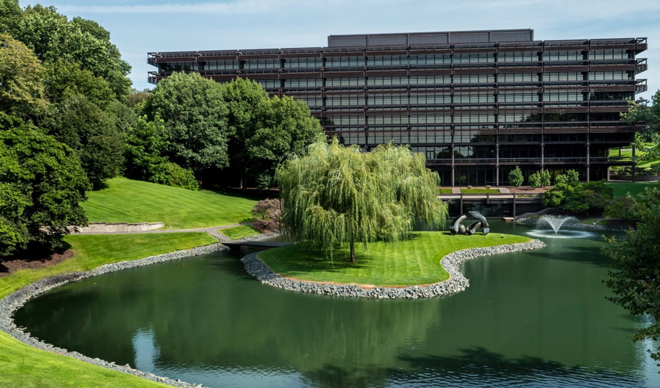 Aerial front view of the John Deere headquarter building with the pond and trees in the foreground