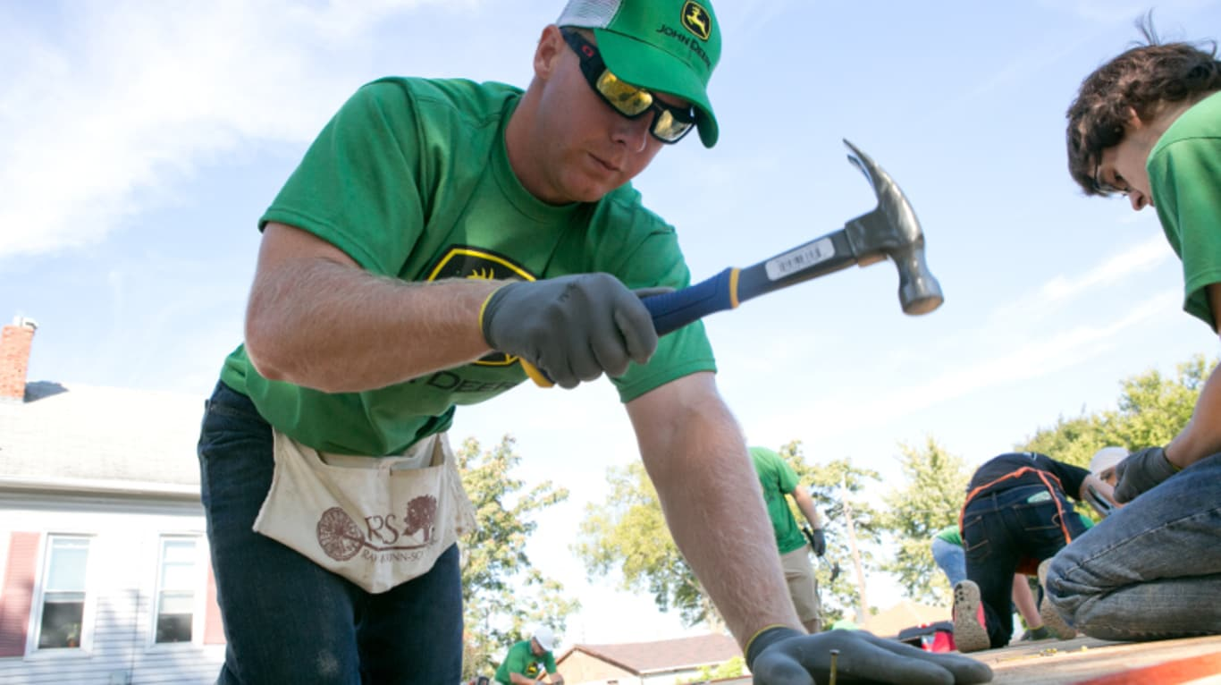 John Deere employee hammering nails during a Habitat for Humanity project