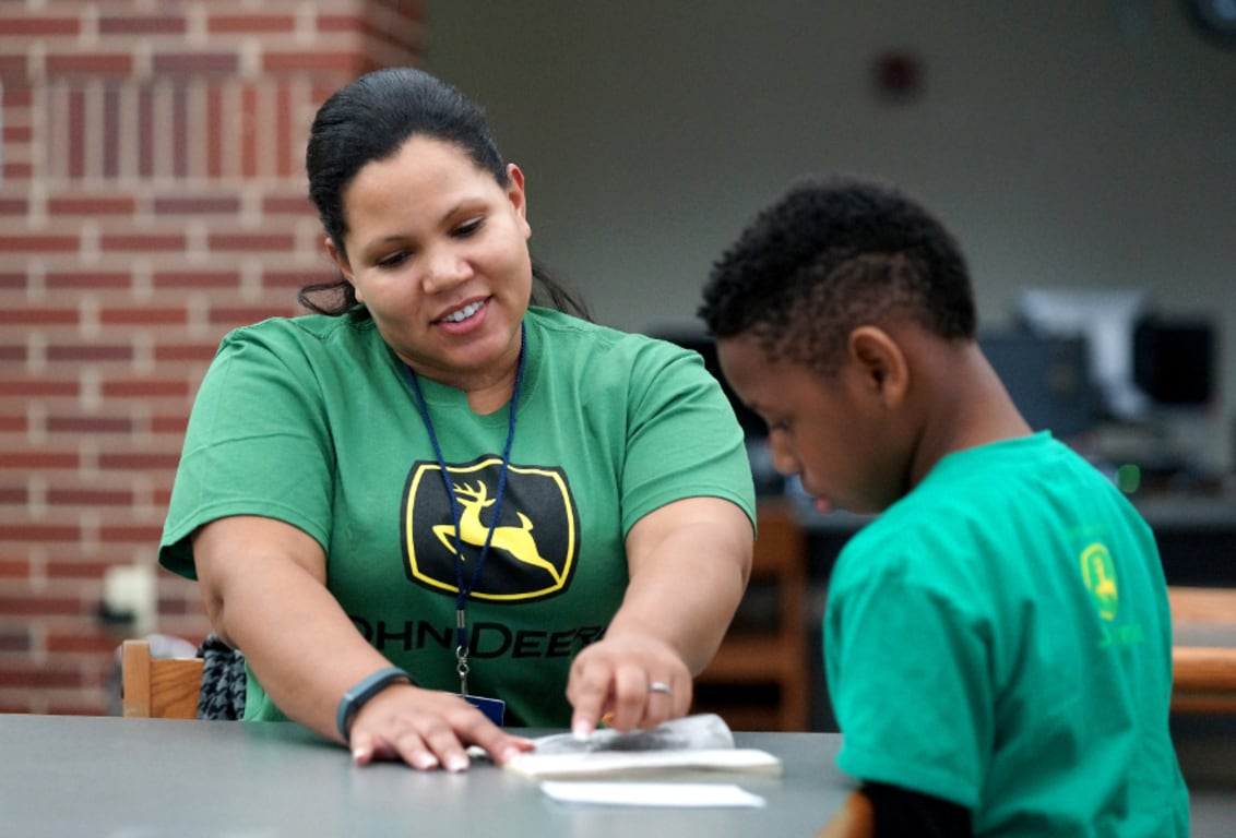 John Deere employee volunteering to assist a student with reading